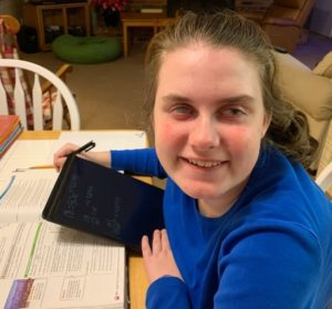 Young lady with aniridia works on computer tablet